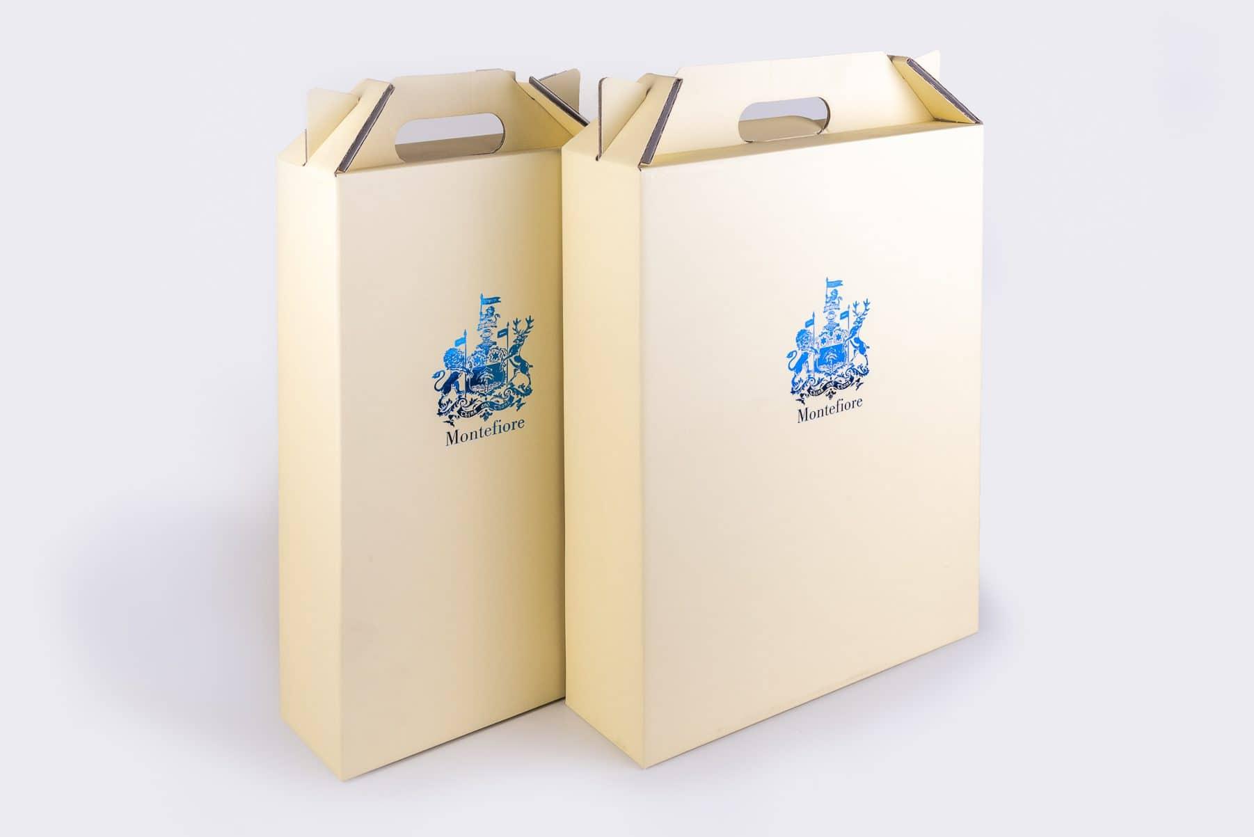 אריזות מתנה בעיצוב אישי שמכיל בקבוקי יין שעוצב ונוצר עבור יק במונטיפיורי. מארז קלאסית בצבע שמנת עם לוגו כחול. שימוש בשטנץ ייחודי בהדפסה לקיפולים המיוחדים.