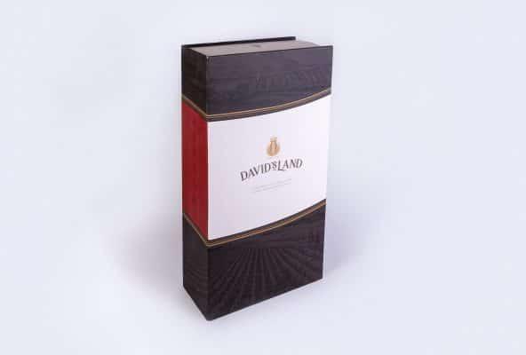 בית דפוס שלנו עיצוב ויצר אריזות קרטון לבקבוקי יין ממותגים של David's Land. המארז דומה לספר בצבעים כחול, לבן, אדום עם תמונה של שדות ענבים ופס מוזהב בעזרת הטבעת פוייל
