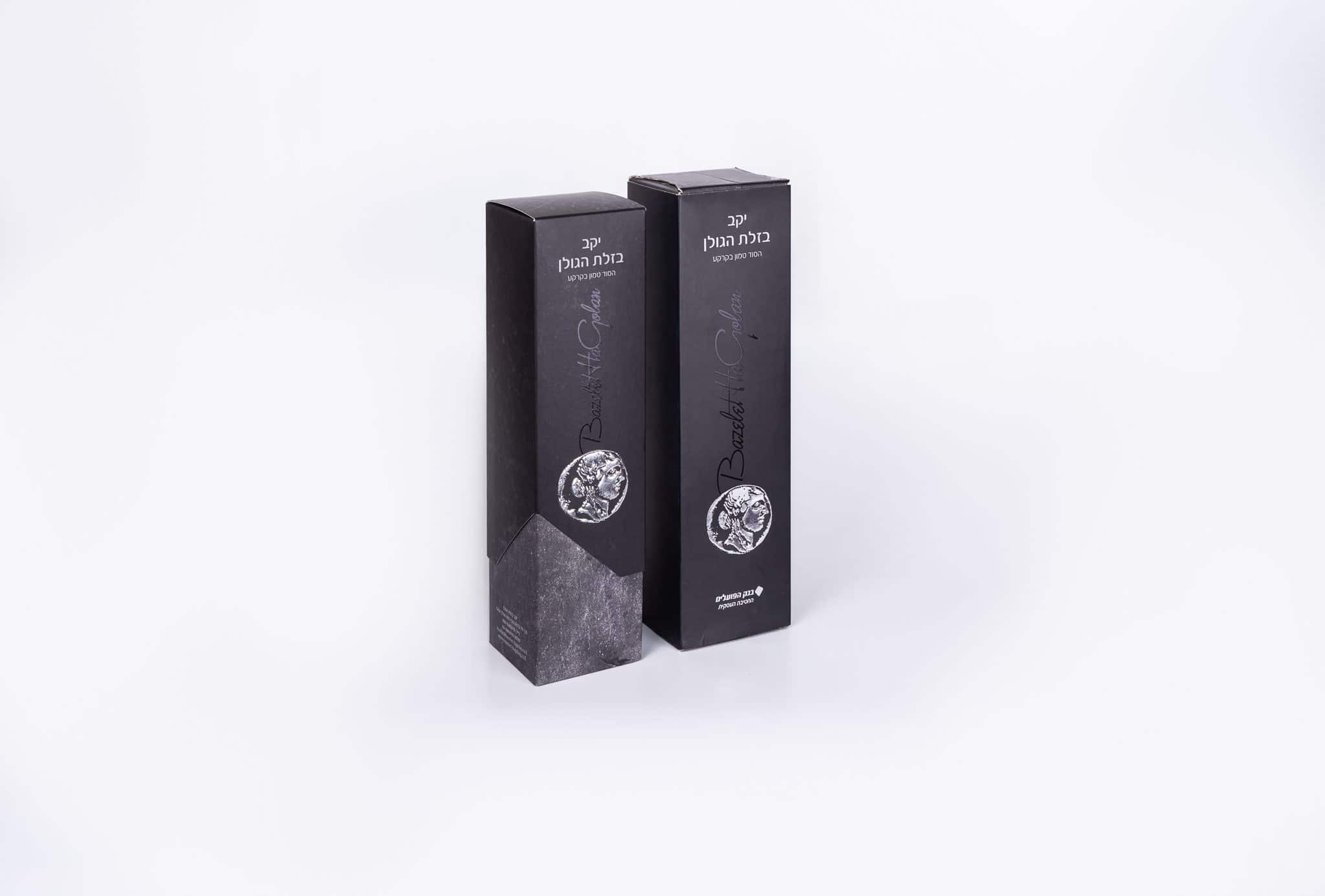 שתי אריזות יוקרתיות מקרטון גלי ומקרטון דחוס לבקבוקי יין של יקב בזלת הגולן. המארזים בצבע שחור עם כתב אפור. יש הבלטה מוזהבת וכסופה על המארז, שטנץ ייחודי לחיתוך וביג מיוחד לקיפול