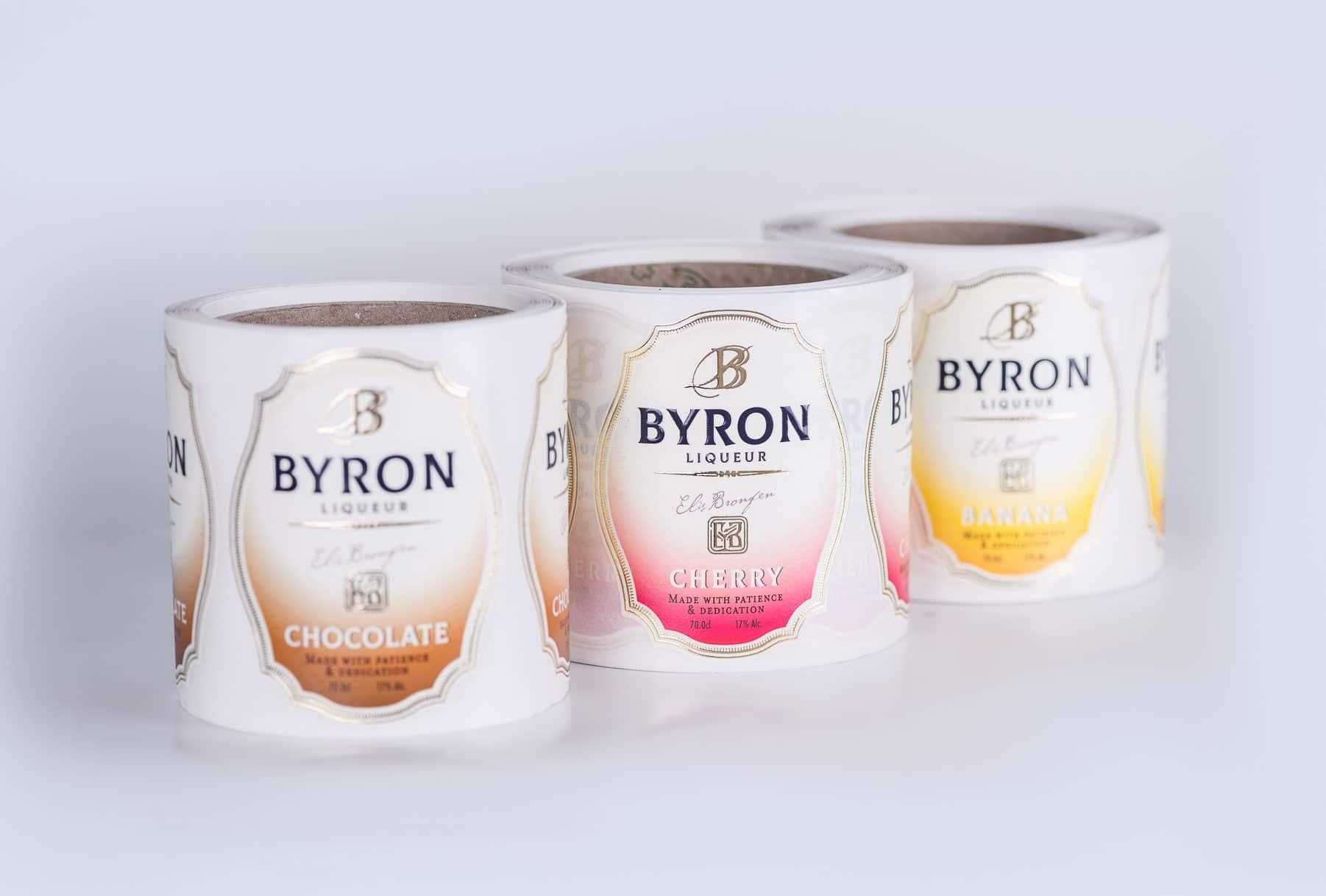שלושה גלילים של תוויות יין שהודפסו עבור בקבוקי יין וליקר של חברת BYRON בצבע חום, ורוד וצהוב. בקבוק עם תווית החומה עשוי משוקולד, ורוד עשוי מדובדבן והצהוב מבננה