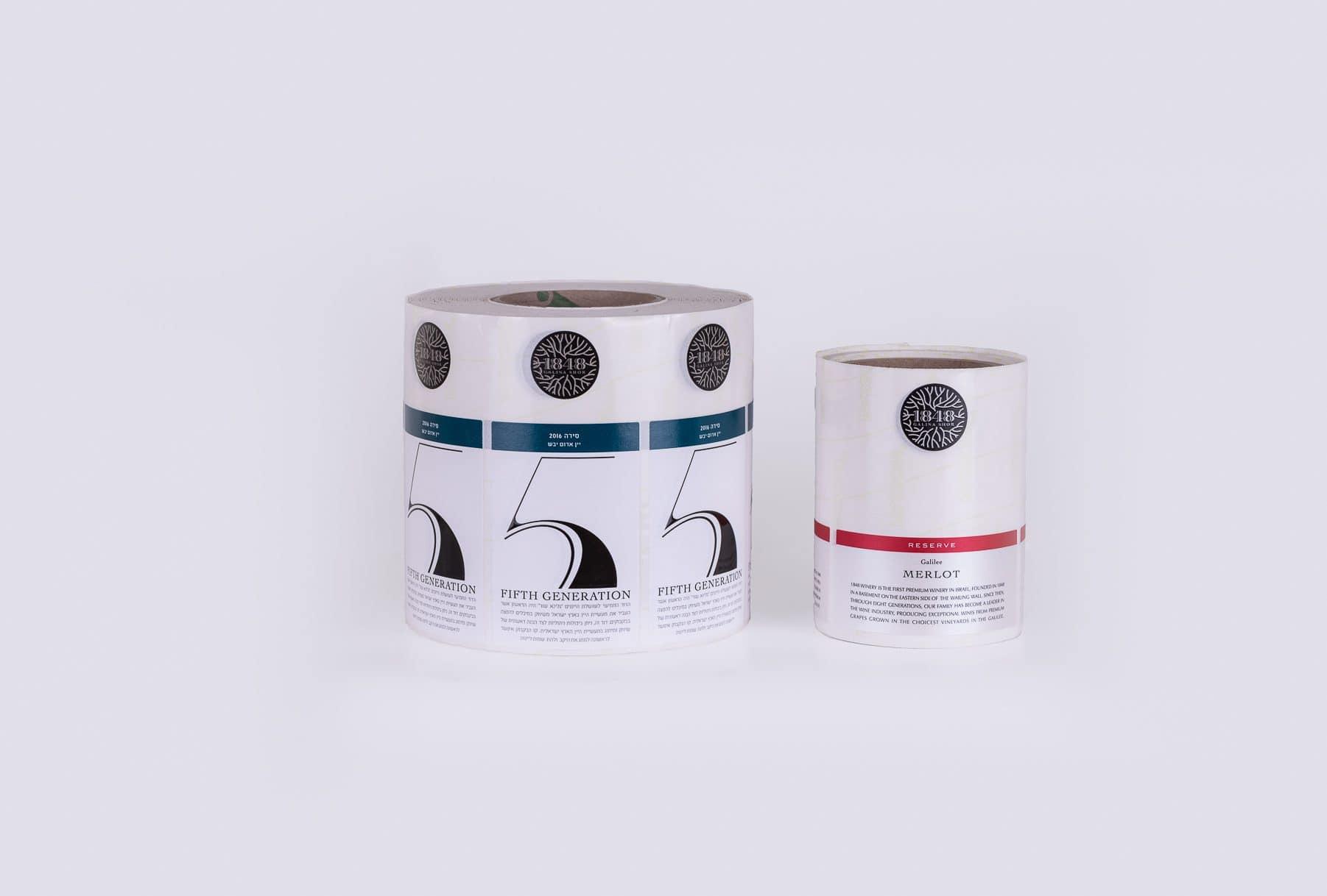 הדפסת גליל תוויות לבנה עם פס כחול ליין אדום יבש,מהדורה חמישית, שנת בציר 2016 ובנוסף תוויות לבנה עם פס אדום ליין MERLOT של יקב 1818