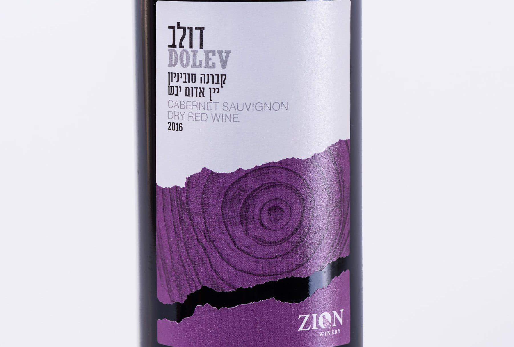 בקבוק יין של יקב דולב עם תווית על הבקבוק בצבע לבן וסגול. כתוב על תווית הבקבוק שהוא יין אדום יבש, קברנה סוביניון, שנת בציר 2016