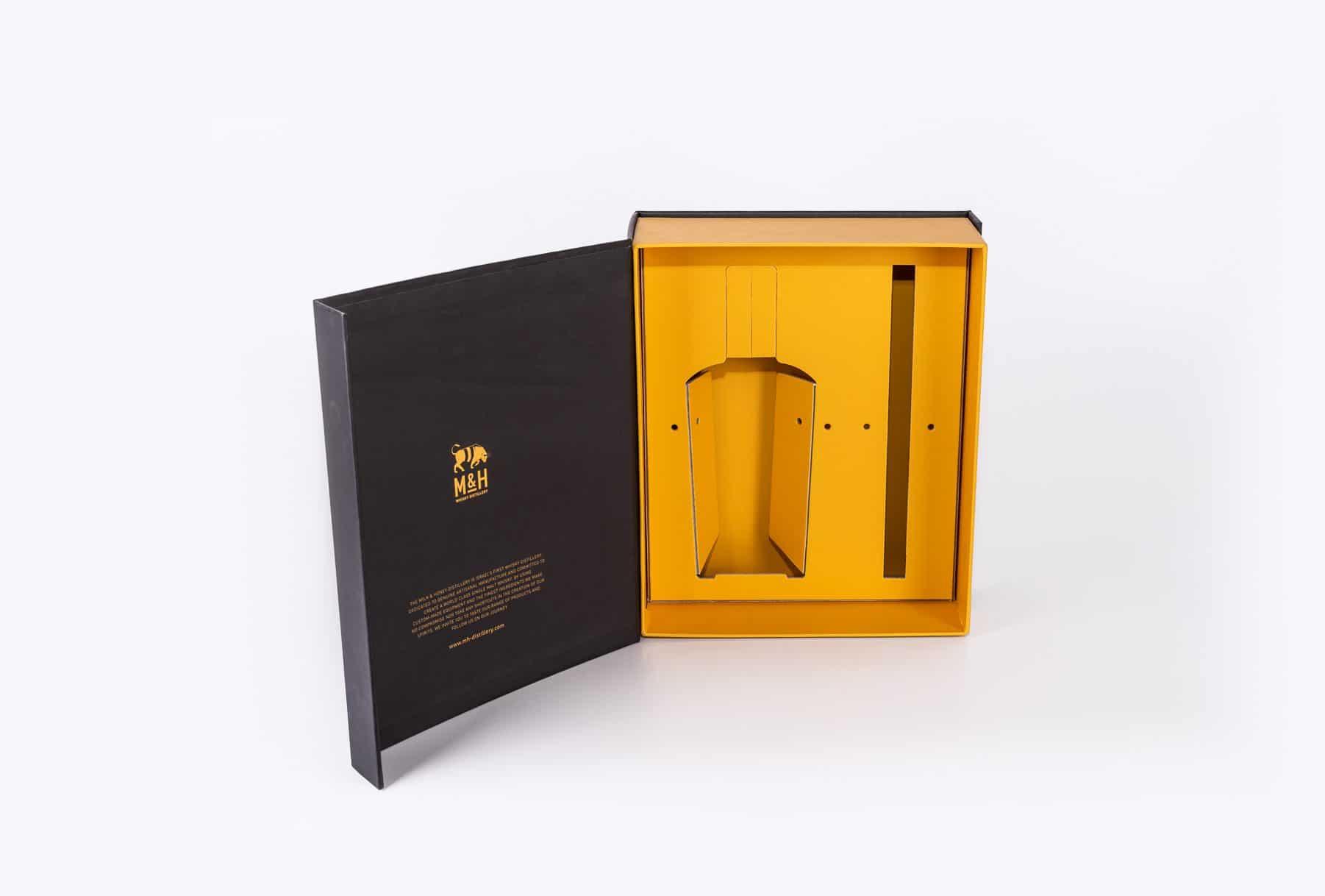 מארזים קשיחים יוקרתיים לוויסקי M&H בצבע שחור מבחוץ ובפנים בצבע צהוב. האריזה עשויה מסוגי קרטונים שונים: קרטון גלי, קרטון דחוס ועוד עם השבחות דפוס: הבלטה והטבעה בחום. שיטת דפוס: דיגיטלי ואופסט