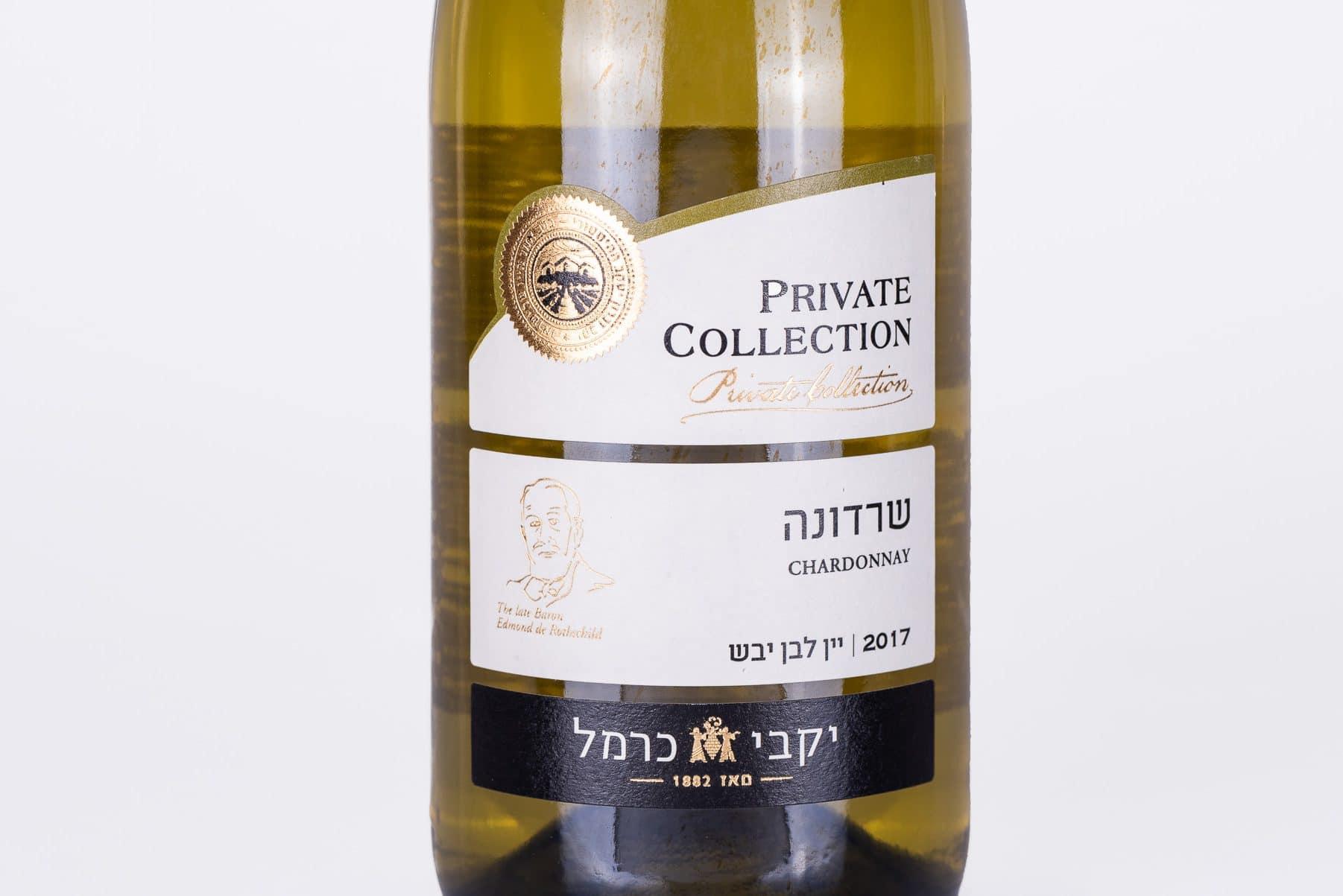יין שרדונה של יקבי כרמל. תוויות לבקבוקי היין הינו בצבע לבן עם פס שחור למטה וחותמת איכות בצבע זהב. יין בניחוחות של אגסים, אפרסקים, בריוש ווניל.