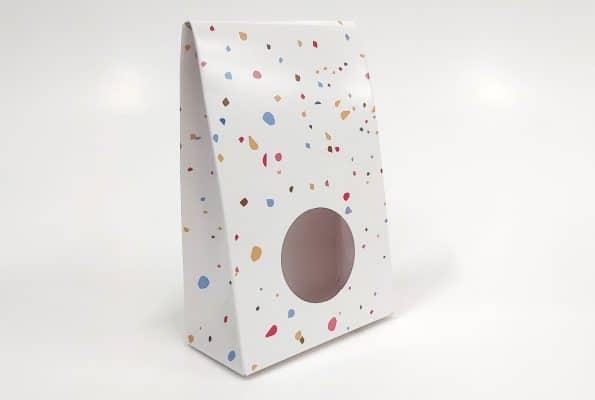 עיצוב אריזות יצירתי בצבע לבן, מצופה בלמינציה עם מלא נקודות צבעוניות ועיגול באמצע.