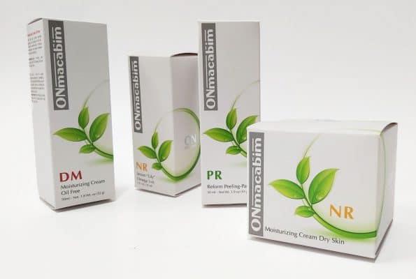 ארבע גדלים שונים של אריזות לקוסמטיקה עבור חברת Onmacabim המתמחים בקוסמטיקה מקצועית. המארזים בצבעי לבן, ירוק ואפור. יש לכה סלקטיבית על העלים